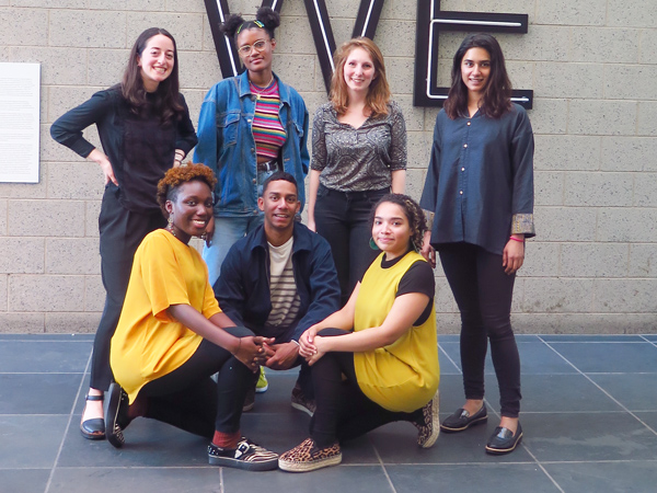 Seven young adults posing for a portrait in front of Glenn Ligon's work