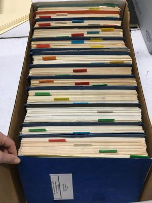 Multiple blue binders with multicolor tabs between aged paper inside a cardboard box.